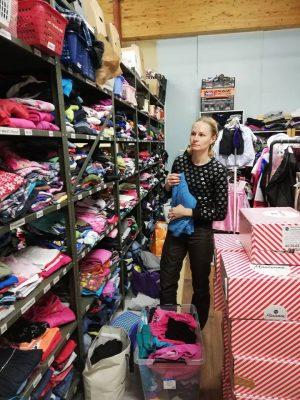 Hope ry:n vapaaehtoinen lajittelee lahjoitettuja lasten vaatteita.