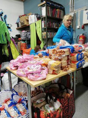 Hope ry:n vapaaehtoinen lajittelee lahjoitettuja leipäpaketteja.