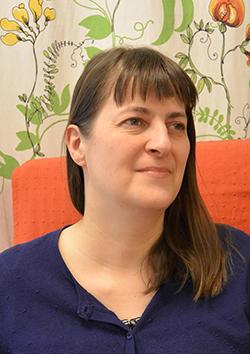 Rintakuvassa Tanja Juvani, taustalla tuolinselkämys ja kukkaköynnösverhot