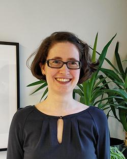 Rintakuvassa Emma Andersson hymyilee iloisesti. Taustalla näkyy pala vaaleaa taulua ja viherkasveja.