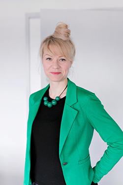 Puolivartalokuvassa Heidi Härmä. Taustalla valkoinen seinä ja raollaan olevan ovi.