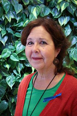 Rintakuvassa Marja Vuorinen, taustalla vihersseinä.