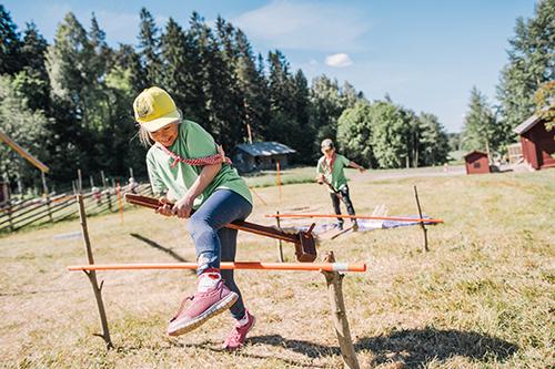 Kaksi lasta esteratsastaa keppihevosilla aurinkoisena päivänä maalaismaisemassa.