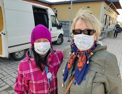 Kaksi naista maskit kasvoilla ja takit päällä ulkona.