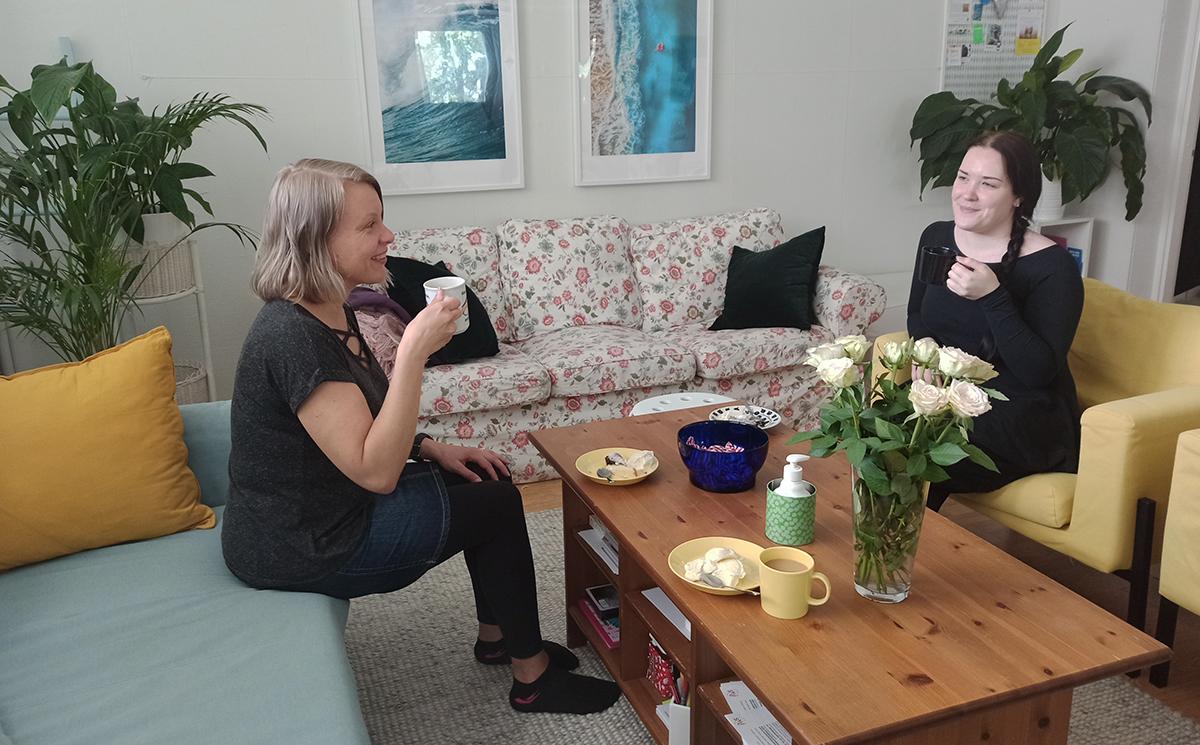 Kaksi naista kahvittelee olohuoneen näköisessä tilassa. Taustalla tauluja ja viherkasveja, pöydällä vaalea ruusukimppu.