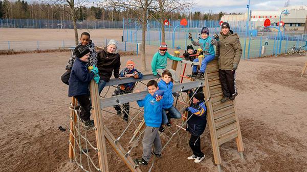 Pelikentän laidalla alakouluikäisiä lapsia kiipeilytelineessä, mukana pari aikuista. Yhdellä lapsella kädessä amerikkalainen jalkapallo. Taustalla lehdettömiä puita.