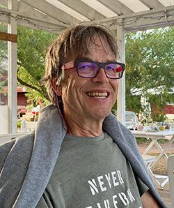 Katetulla terassilla hymyilee Jorma Sipilä T-paita päällä, college hartioillaan.