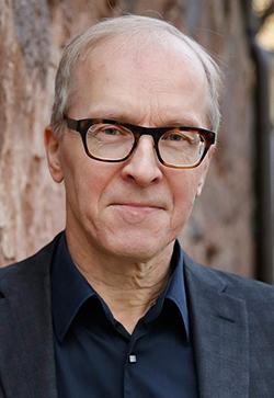 Kasvokuvassa Sakari Heikkinen, taustalla näkyy havupuun runkoa.