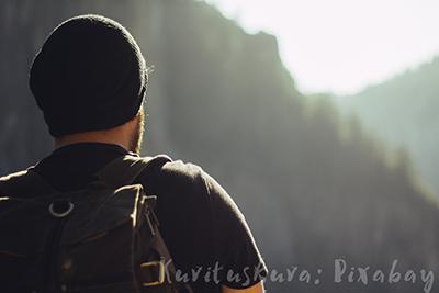 Pipopäinen, reppuselkäinen mies takaapäin kirkkaaseen vastavaloon kuvattuna, edessä häämöttää korkeita mäkiä.