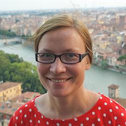 Rintakuvassa hymyilee Marjo Salmela. Kuva on otettu näköalapaikalta, taustalla näkyy jokin ehkä eurooppalainen kaupunki ja sitä halkova leveä joki.