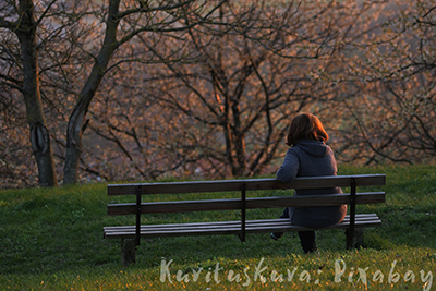 Takaa kuvattu puistonpenkki, jolla istuu nainen, jonka punaisiin hiuksiin laskevan auringon säteet osuvat. Hämyisä kuva syksyisestä puistosta.