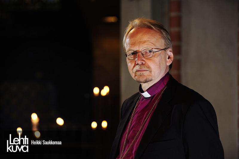 Rintakuvassa Kari Mäkinen lilassa papinpaidassa, hämyisessä tilassa, jossa näkyy useita kynttilöiden liekkejä.