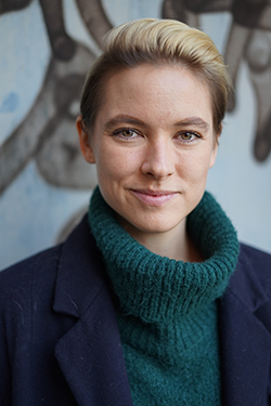 Sara Mäkäräinen rintakuvassa villapaita ja takki päällä.