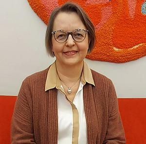 Eija Koivuranta katsoo rintakuvassa hymyillen kameraan, taustalla oranssi tuolinselkä ja seinävaate.